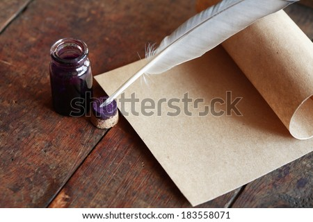 Paper and quill pen on nice old wooden background - stock photo