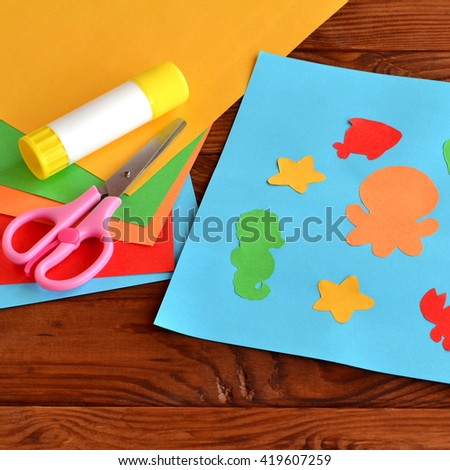 Paper applique with sea animals and fishes. Art lesson in kindergarten. Paper sea animals - octopus, fish, starfish, seahorse, crab. Kids diy. Sheets of colored paper, scissors, glue  - stock photo