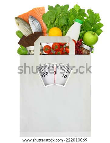 Paper bag full of groceries with weighing scale - stock photo