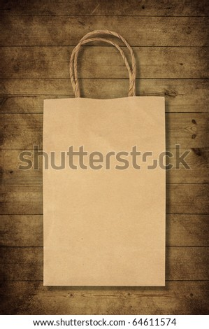 paper bag on old wooden background for natural recycle concept - stock photo
