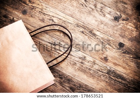 Paper bag rustic wooden background. - stock photo