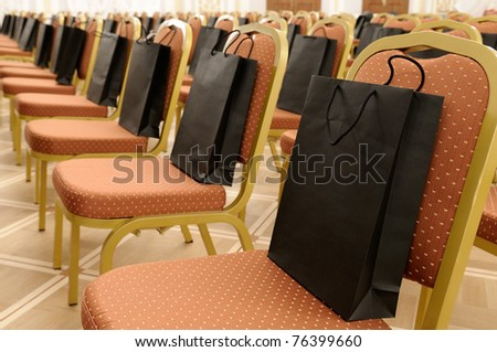 Paper bags on chairs in the conference hall.