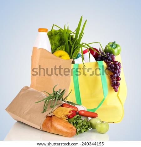 Paper bags with products on light grey background - stock photo
