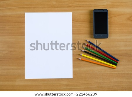 Paper blank Sheet, color pencils, smartphone on wooden table. Paper blank Sheet, color pencils, smartphone on wooden table. - stock photo