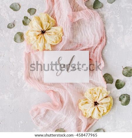 paper blank with word sale, dry white tulips, eucalyptus petals and pink textile on concrete background. Flat lay, top view - stock photo
