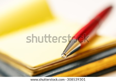 Paper blocks with pen on it in closeup - stock photo