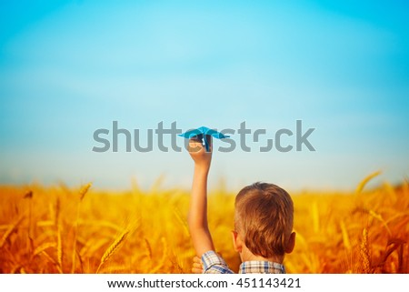 Paper blue airplane in children hands on yellow wheat field  and blue sky in summer  day - stock photo