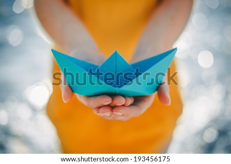 Paper Boat in human hands - stock photo