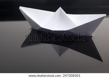 Paper boat in water - stock photo