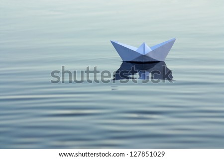 Paper boat on the river - stock photo