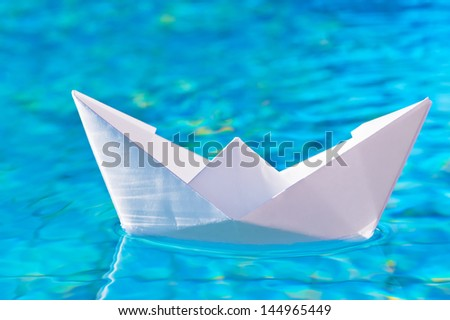 paper boat on the water in the pool - stock photo