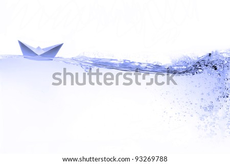 Paper boat on water wave - stock photo
