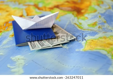 Paper boat, passport, money on a background map of the world. Traveling concept - stock photo