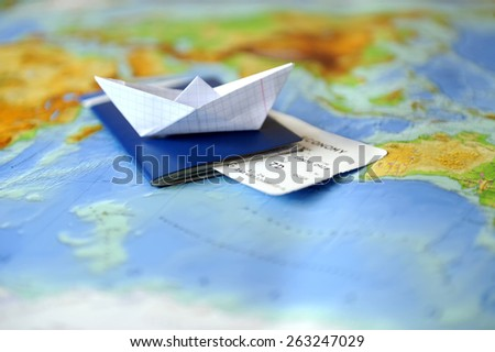 Paper boat, passport on a background map of the world. Traveling concept - stock photo