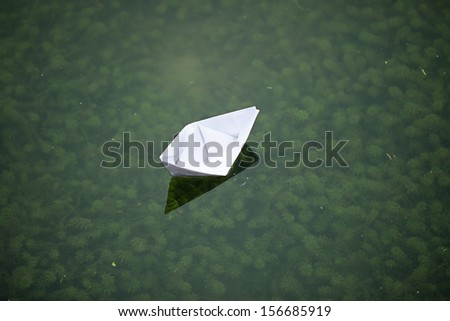 paper boat sailing in lake with peace - stock photo
