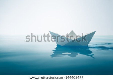 paper boat sailing on water with waves and ripples - stock photo