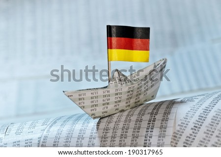 Paper boat with German flag shipping on stock market news. - stock photo