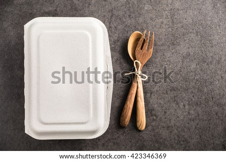 paper box for takeaway with spoon and fork wood on old marble background - stock photo