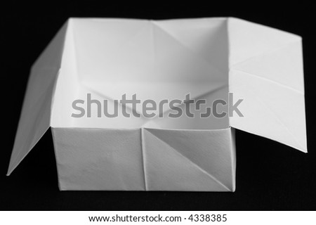 Paper box - simple origami on a black background - stock photo