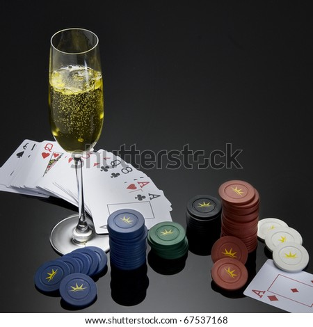 paper card chips and a glass of champagne on black gradient background like a table - stock photo