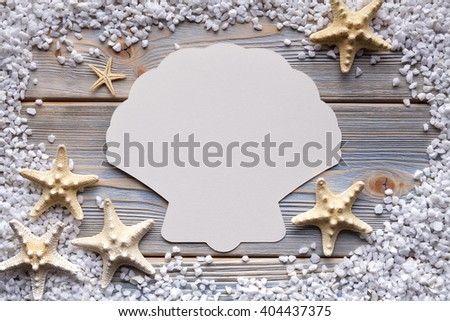 Paper card in the shape of shells on wooden boards - stock photo