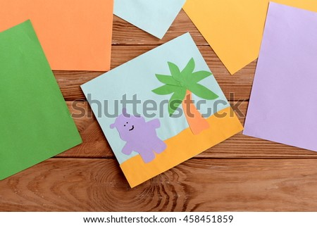 Paper card with happy hippo and a palm tree, colored paper sheets on a wooden table. Kindergarten art and craft activity for kids. Fun children background  - stock photo