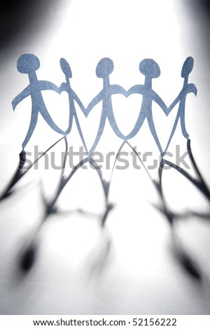 Paper-chain people holding hands in a row - stock photo