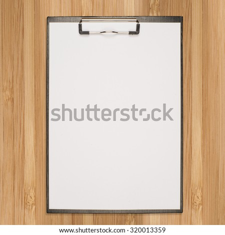 paper clipboard on wood background and texture