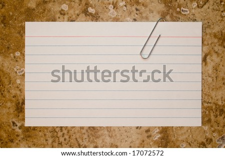Paper-clipped note card on stone background - stock photo