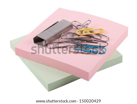 paper clips and staples are on two packs of stickers on a white background
