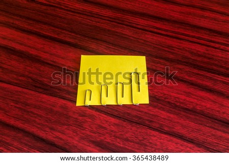 Paper clips attached by size on a yellow note. - stock photo