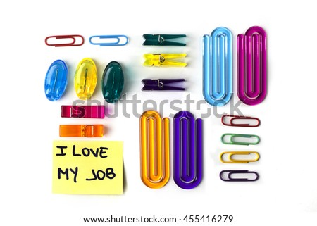 Paper clips set and yellow paper note with the words I love my job isolated over a white background - stock photo