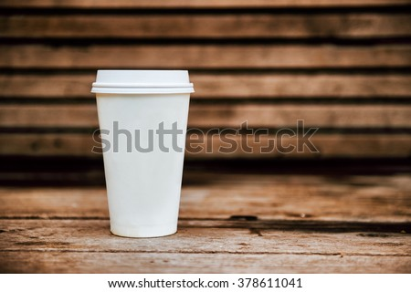 Paper coffee cup from coffee shop on wooden background - stock photo