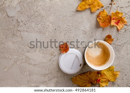 Paper coffee cup on the autumn fall leaves and stone surface background, selective focus