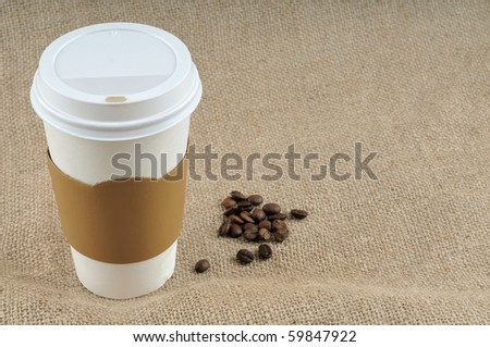 Paper coffee cup with safety cardboard collar on jute background with a big copy space - stock photo