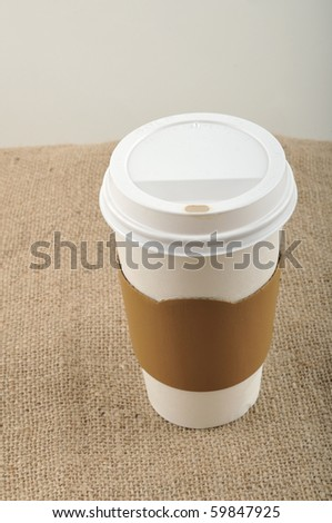 Paper coffee cup with safety cardboard collar on jute background with a copy space. - stock photo