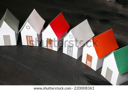 Paper craft houses in a row on a dark wooden surface