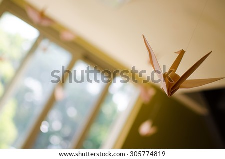 Paper cranes hanging from the ceiling. Only one of the paper cranes is clear in the view due to selective focus. It seems that cranes are flying toward the bright-lit window. Selective focus. - stock photo