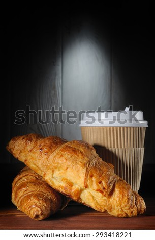 Paper cup of coffee and two croissants on wooden background with color backlight - stock photo
