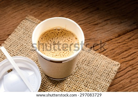 Paper cup of coffee on wood board - stock photo