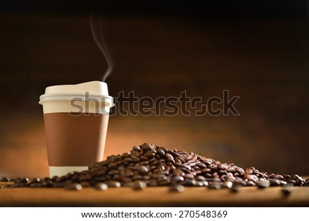 Paper cup of coffee with smoke and coffee beans on old wooden background - stock photo