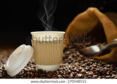 Paper cup of coffee with smoke and coffee beans on wooden table - stock photo