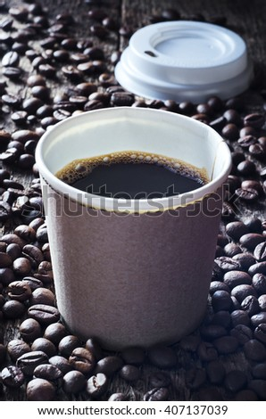 Paper cup of fresh hot coffee and coffee beans on wooden table.