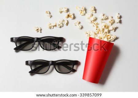 paper cup with popcorn and 3D glasses on white background. mock up. top view. - stock photo