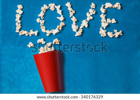 paper cup with popcorn lined word on blue background. mock up. top view. - stock photo
