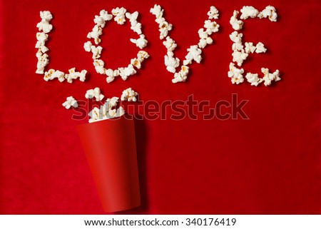 paper cup with popcorn lined word on red background. mock up. top view. - stock photo
