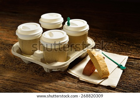 Paper cups of coffee and biscotti on wooden background - stock photo