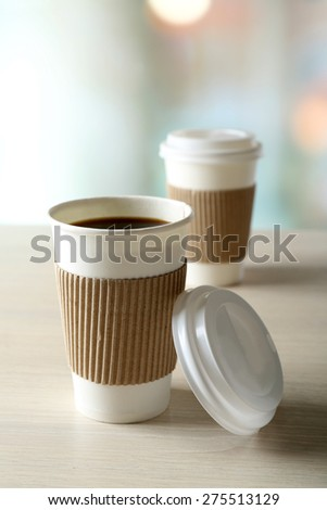 Paper cups of coffee on table on bright background - stock photo