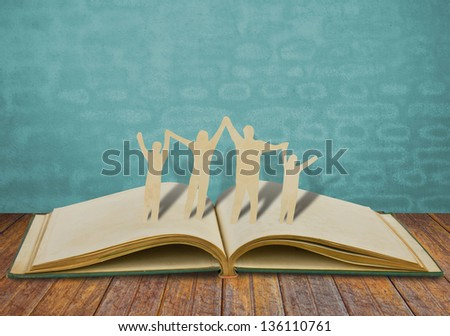 Paper cut family symbol on old book - stock photo