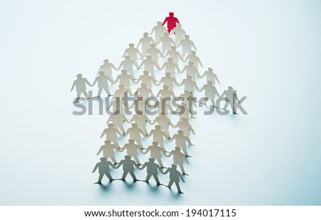 Paper cut figures standing to form of an arrow - stock photo